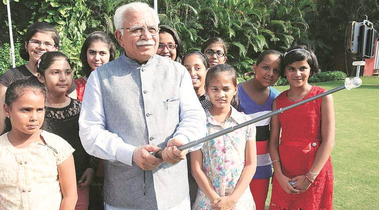 Haryana Chief Minister Manohar Lal clicking a selfie with girls as they called on him to thank him for launching `Beti Bachao-Beti Padhao' campaign at his residence in Chandigarh on Friday, July 17 2015. Express photo