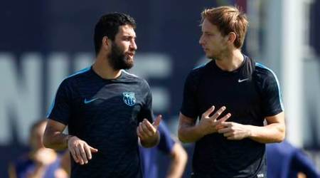 FC Barcelona's Arda Turan, left, talks with his teammate Ivan Rakitic during a training session at the Sports Center FC Barcelona Joan Gamper in San Joan Despi, Spain, Monday, Sept. 28, 2015.  FC Barcelona will play against Bayer Leverkusen during a Champions League Group E on Tuesday . (AP Photo/Manu Fernandez)