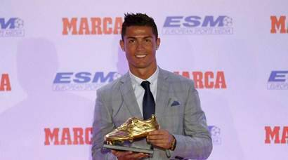 MADRID:  Real Madrid's striker Cristiano Ronaldo poses with the Golden Boot award for scoring the most goals in Europe's domestic leagues last season during a ceremony in Madrid, Spain Tuesday Oct. 13, 2015. This is the fourth Golden Boot award Ronaldo has won during his career and his third since joining Real Madrid, where he scored 48 goals during the last La Liga season. AP/PTI(AP10_13_2015_000215A)