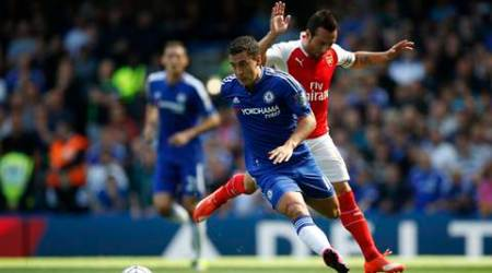 Chelsea's Eden Hazard, let gets past a tackle by Arsenal's Santi Cazorla during the English Premier League soccer match between Chelsea and Arsenal at Stamford Bridge stadium in London, Saturday, Sept. 19, 2015. Chelsea won the game 2-0. (AP Photo/Alastair Grant)