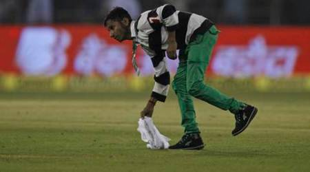 A member of the ground staff removes materials thrown by spectators during the second Twenty20 cricket match between India and South Africa in Cuttack, India, Monday, Oct. 5, 2015. (AP Photo/Biswaranjan Rout)