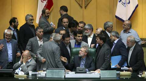 Iran's parliament speaker Ali Larijani, center, speaks with lawmakers in an open session of parliament while discussing a bill on Iran's nuclear deal with world powers, in Tehran, Iran, Sunday, Oct. 11, 2015. (AP Photo)
