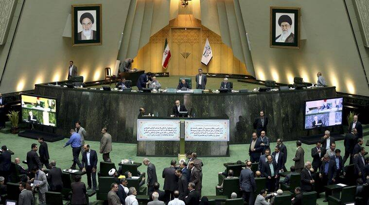 In this photo taken on Sunday, Oct. 11, 2015, head of Iran's Atomic Energy Organization Ali Akbar Salehi, center, ends his speech in an open session of parliament while discussing a bill on Iran's nuclear deal with world powers, in Tehran, Iran. Iran's parliament voted Tuesday to support implementing a landmark nuclear deal struck with world powers despite hard-line attempts to derail the bill, suggesting the historic accord will be carried out. (AP Photo/Ebrahim Noroozi)
