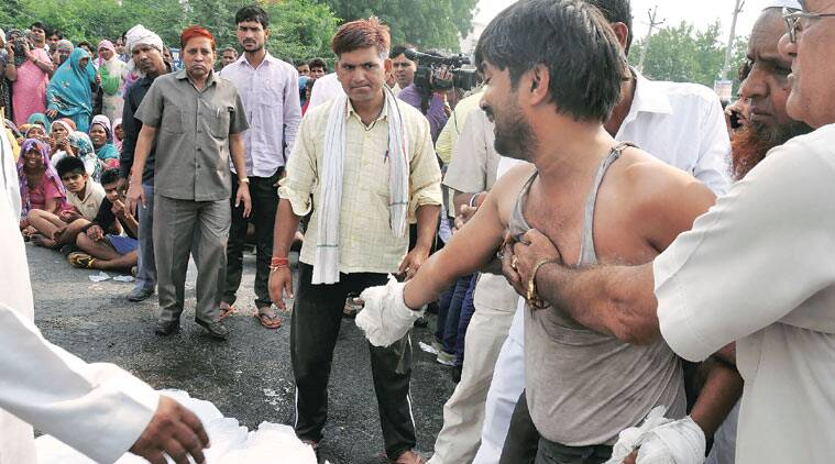 Jitender with the bodies of his two children on the highway, Wednesday. (Source: Express photo by Manoj Kumar)