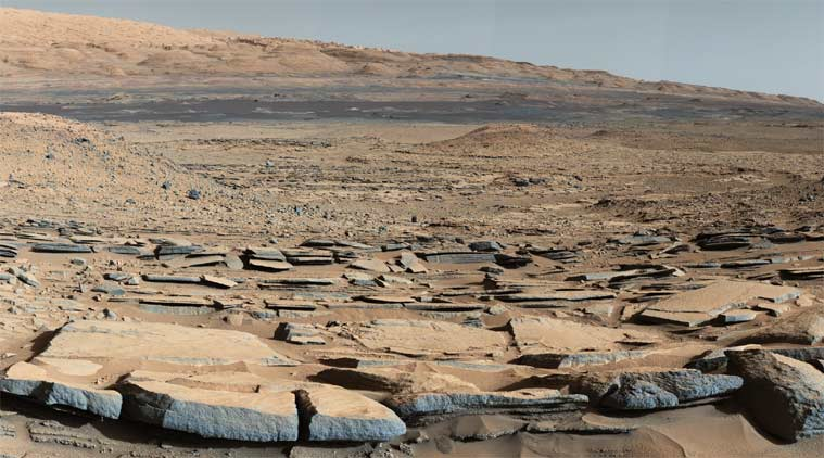 "A view from the ""Kimberley"" formation on Mars taken by NASA's Curiosity rover. The strata in the foreground dip towards the base of Mount Sharp, indicating flow of water toward a basin that existed before the larger bulk of the mountain formed. (Source: NASA)"