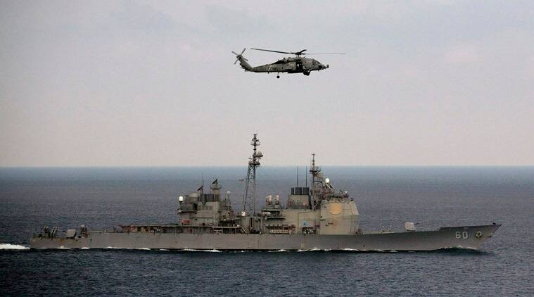 A U.S. Navy helicopter approaches to land on the deck of aircraft carrier USS Theodore Roosevelt (CVN 71), a missile cruiser and a nuclear-powered submarine, as the USS Normady sails in the Bay of Bengal during Exercise Malabar 2015, some 152 miles off eastern coast of Chennai, India, Saturday, Oct. 17, 2015. Naval warships, aircraft carriers and submarines from the U.S., India and Japan are conducting joint military exercises off India's east coast, signaling the growing strategic ties between the three navies as they face up to a rising China. (AP Photo/Arun Sankar K.)