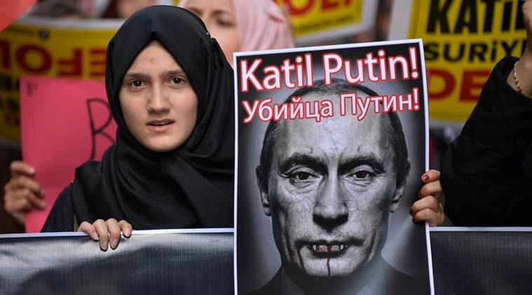 A demonstrator holds a picture depicting Russian President Vladimir Putin during a protest against Russian military operations in Syria, in Istanbul, Turkey. AP Photo