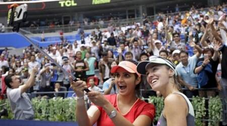 Martina Hingis of Switzerland (R) and Sania Mirza of India pose for pictures as they celebrate after winning their women's doubles final match against Irina-Camelia Begu and Monica Niculescu of Romania, at the Wuhan Open tennis tournament, Hubei province, October 3, 2015. REUTERS/China Daily CHINA OUT. NO COMMERCIAL OR EDITORIAL SALES IN CHINA