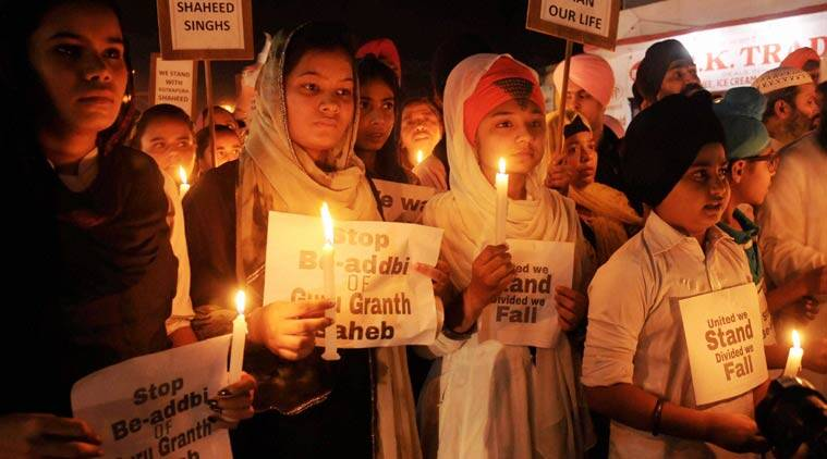Sikhs Children taking out a candle march during their protest against the alleged desecration of religious book and Punjab firing incident in Amritsar on Tuesday. (PTI Photo)
