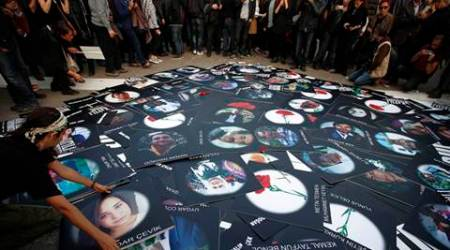 """A woman displays the image of one of the victims as thousands of people gather to commemorate the first week anniversary of twin Ankara blasts that claimed 102 lives, in Istanbul, Turkey, Saturday, Oct. 17, 2015. The commemoration started at 10:04am (local), the time the bombs went off last Saturday, and the crowd stood in silence in memory of the deceased victims. The banner reads: """" We know the assassin."""" (AP Photo/Emrah Gurel)"""