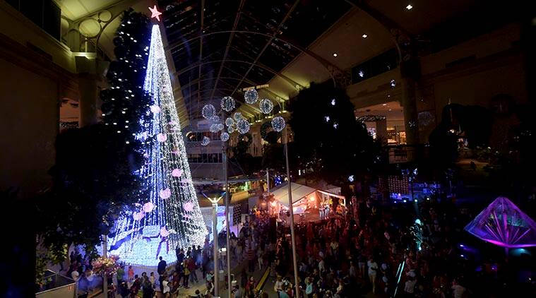 In this Friday, Nov. 27, 2015 photo, people gather to observe a Guinness World Records attempt for the most lights on an artificial Christmas tree in Canberra, Australia. Australian David Richards set his third Christmas-themed world record in as many years Friday by illuminating a tree in downtown Canberra with 518,838 twinkling lights. Guinness World Records confirmed that Richards had broken the record for the most lights on an artificial Christmas tree that had been held for five years by Universal Studios Japan in Osaka. (Lukas Coch/AAP Via AP) AUSTRALIA OUT, NEW ZEALAND OUT, PAPUA NEW GUINEA OUT, SOUTH PACIFIC OUT, NO SALES, NO ARCHIVES