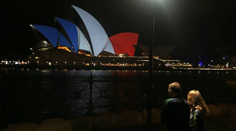 A couple look at the sails of the Sydney Opera House that are lit in the colors of the French flag in Sydney, Saturday, Nov. 14, 2015, following the terrorist attacks in Paris. French police are huntingfor possible accomplices of assailants who terrorized Paris concert-goers, cafe diners and soccer fans in the country's deadliest peacetime attacks, a succession of explosions and shootings that cast a dark shadow over this luminous tourist destination. (AP Photo/Rick Rycroft)