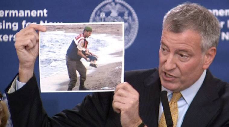 In this Nov. 18, 2015, frame from video, New York City Mayor Bill de Blasio displays a photo of Aylan Kurdi. (Source: AP)