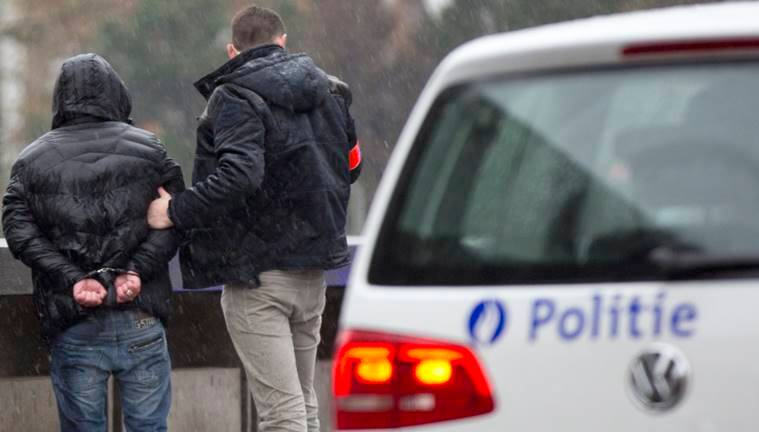 Police detain a man in handcuffs after stopping and searching his car which had French number plates in Brussels. (AP Photo/Virginia Mayo)