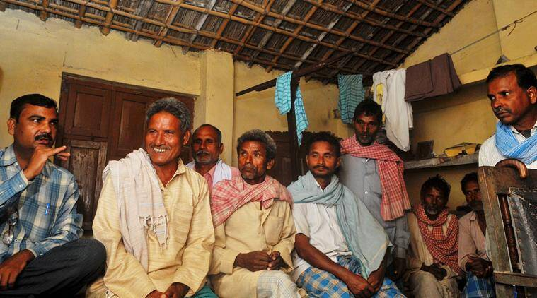 Sunil Sahni (left) alongwith other villagers of thier Nishad (Sahni)caste holds a discussion for the assembly election in Dumri in Muzaffarpur. Express Photo By Prashant Ravi