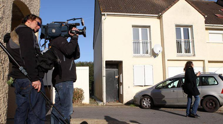 Journalists stand in front of the house where neighbors say French suicide bomber Ismael Omar Mostefai lived with his family until about two years ago in Chartres, France, Sunday, Nov. 15, 2015. Thousands of French troops deployed around Paris on Sunday and tourist sites stood shuttered in one of the most visited cities on Earth while investigators questioned the relatives of a suspected suicide bomber involved in the country's deadliest violence since World War II. (AP Photo/Michel Spingler)