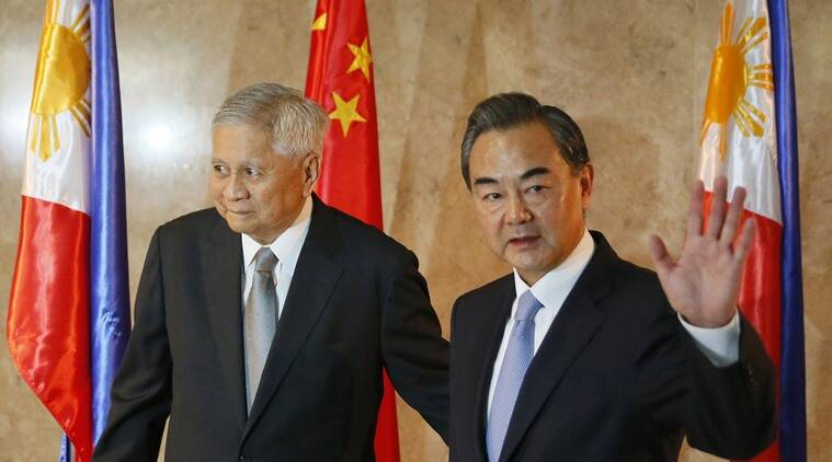 Chinese Foreign Minster Wang Yi waves to the media as he arrives at the Department of Foreign Affairs for talks with Philippine Foreign Secretary Albert Del Rosario, left, Tuesday, Nov.10, 2015 at suburban Pasay city, south of Manila, Philippines. It was Wang's first visit to the country amid the two countries' row over the Spratlys group of islands in the South China Sea. (AP Photo/Bullit Marquez)