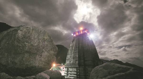 Bhim Shila and the Kedarnath temple. Pilgrims have started to offer prayers to the boulder (left) that diverted the flow of water and rocks and thereby reducing the stress on the temple during the flash floods of 2013. (Source: Express photo by Oinam Anand)
