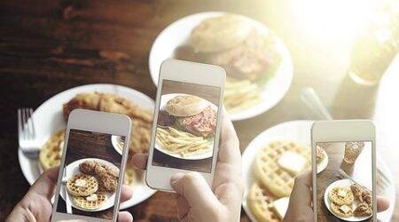 friends taking photos of food with smart phones