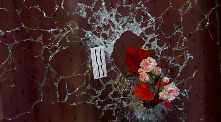 Flowers are put in a window shattered by a bullet as a forensic marker sits next to the impact as people pay their respect to the victims at the site of the attacks on restaurant Le Petit Cambodge (Little Cambodia) and the Carillon Hotel on the first of three days of national mourning in Paris, Sunday, Nov. 15, 2015. (AP Photo)