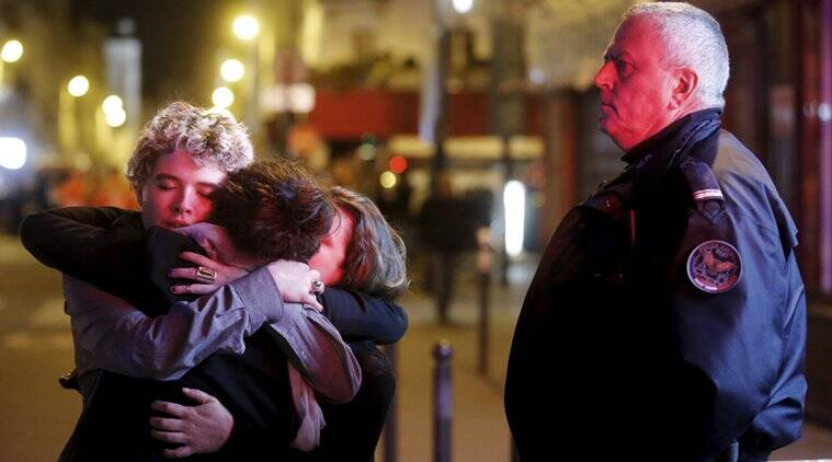 People hug on the street near the Bataclan concert hall following fatal attacks in Paris, France, November 14, 2015. Gunmen and bombers attacked busy restaurants, bars and a concert hall at locations around Paris on Friday evening, killing dozens of people in what a shaken French President described as an unprecedented terrorist attack.    REUTERS/Christian Hartmann