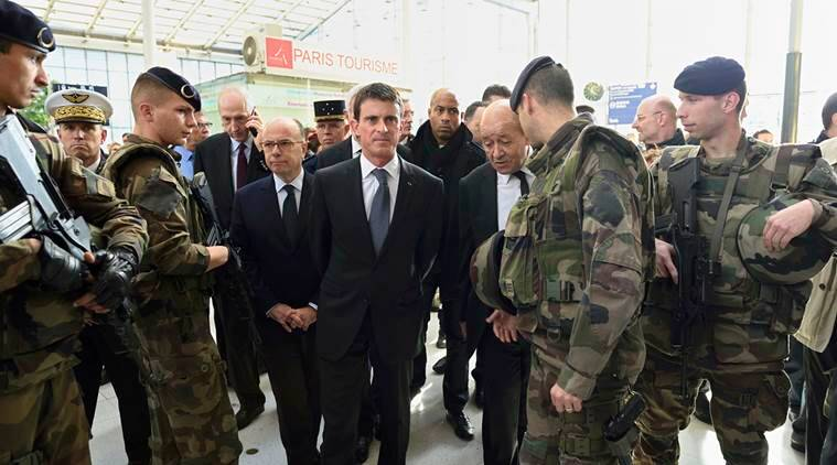 French Prime minister Manuel Valls (C) arrives with French Defence minister Jean-Yves Le Drian (R), French national rail company SNCF Chairman Guillaume Pepy (L Rear) and French Interior minister Bernard Cazeneuve (L) speak with soldiers at the Gare du Nord railway station in Paris, France, November 15, 2015. REUTERS/Eric Feferberg/Pool