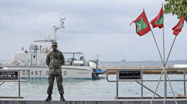 A military person stands guard at a boat jetty next to Maldivian flags erected ahead of Republic Day in Male, Maldives, Thursday, Nov. 5, 2015. Maldives' Parliament voted overwhelmingly on Thursday to impeach the country's vice president, who will be charged with terrorism for plotting to kill the president, a minister said. The president, who was not hurt in the blast, has declared a state of emergency, saying the explosion and subsequent discovery of arms posed a threat to national security. (AP Photo/Sinan Hussain)