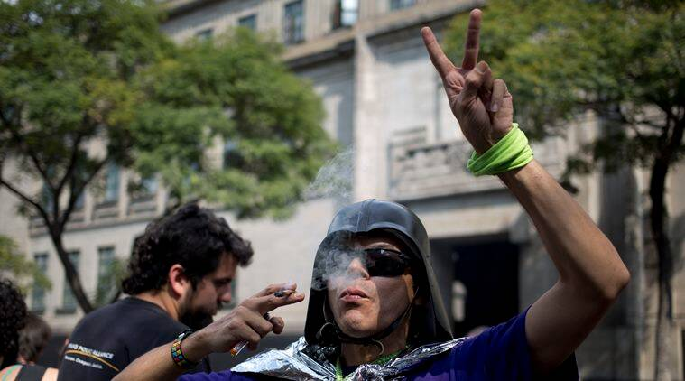 A supporter of marijuana legalization smokes outside the Supreme Court in Mexico City, Wednesday, Nov. 4, 2015. Mexico's court ruled Wednesday that growing, possessing and smoking marijuana for recreation are legal under a person's right to personal freedoms. (AP Photo/Eduardo Verdugo)