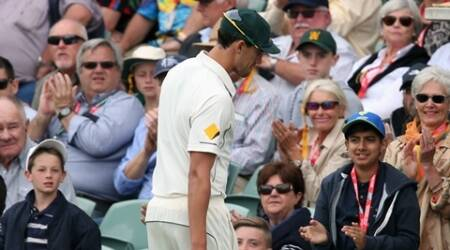 """Australia's Mitchell Starc walks from the field injured during their cricket test against New Zealand in Adelaide, Friday, Nov. 27, 2015. This match is the sport's first ever day-night test and the use of the """"experimental"""" pink leather ball replacing the standard-issue red for the first time in a format that dates back to the 1870s. (AP Photo/Rick Rycroft)"""