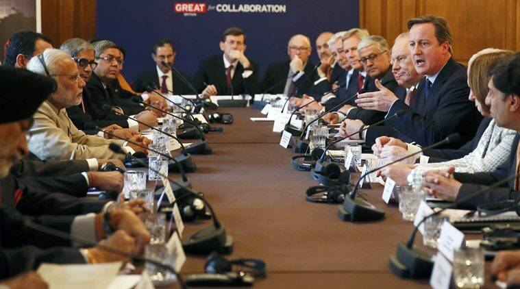 Prime Minister Narendra Modi, left, listens as Prime Minister David Cameron talks, right, during the CEO Forum inside 10 Downing Street in London, Friday Nov. 13, 2015, on the second day of his visit to the UK. Modi and Cameron both vowed Thursday to use U.K. knowhow and investment to help modernize the world's largest democracy, India. (Stefan Wermuth/Pool via AP)