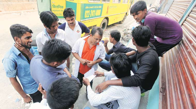 Harish Singh tries to convince migrant workers at the Govandi slum to get themselves tested (Express Photo by  Narendra Vaskar)