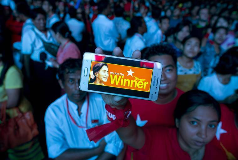 A supporter of Myanmar's National League for Democracy party displays her mobile phone with a picture of Suu Kyi as they gather to celebrate unofficial election results outside the NLD headquarters in Yangon. AP Photo