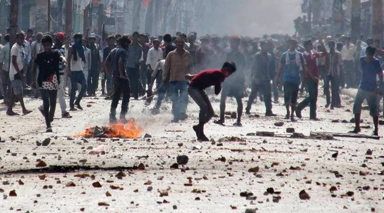 Ethnic Madhesi protesters throw stones and bricks at Nepalese policemen in Birgunj, a town on the border with India, Nepal, Monday, Nov. 2, 2015. Ethnic protesters demonstrating against the new constitution clashed with police in south Nepal Monday which left at least one person killed and several more injured, officials said. (AP Photo/Jiyalal Sah)