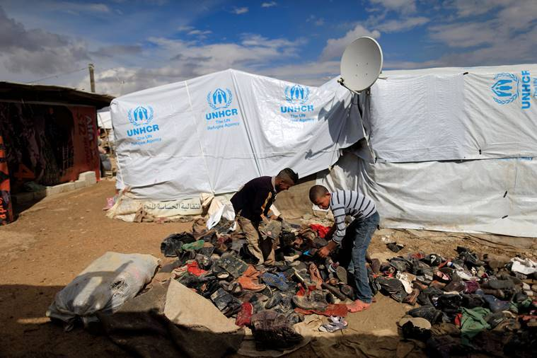 Syrian refugee boys help their family to collect shoes to be added under a fire to boil water outside their family's tent at a refugee camp in the town of Hosh Hareem, in the Bekaa valley, east Lebanon. AP Photo/Hassan Ammar