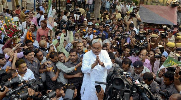 Bihar Chief Minister Nitish Kumar, center, is surrounded by media personnel as he greets supporters after victory in Bihar state elections in Patna. (Source: PTI)