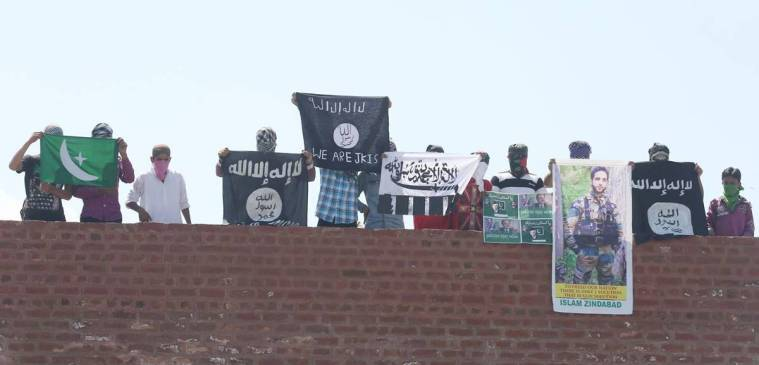 Masked Kashmiri youth hold Islamic State and Lashkar-e-Taiba flags as well as posters of Pakistan founder Ali Mohammad Jinnah during protest outside Jamia Masjid in Srinagar. Express Photo