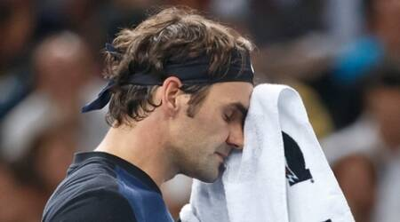 Switzerland's Roger Federer wipes his face returns as he plays American's Joh Isner during their third round match of the BNP Masters tennis tournament at the Paris Bercy Arena, in Paris, France, Thursday, Nov. 5, 2015. Isner won 7-6, 3-6, 7-6. (AP Photo/Michel Euler)
