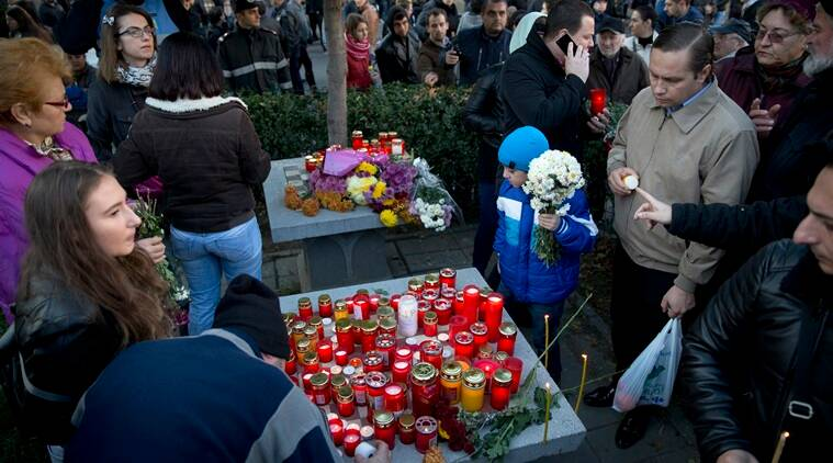 A child holds flowers as people light candles outside the Colectiv nightclub, during a mourning march joined by thousands in Bucharest, Romania. (AP Photo/Vadim Ghirda)