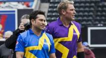 Cricketers Sachin Tendulkar and Shane Warne walk across the pitch before a Cricket All-Star exhibition match at Citi Field in New York