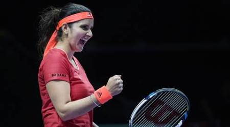 Sania Mirza of India celebrates a point as she and her partner Martina Hingis of Switzerland play Timea Babos of Hungary and Kristina Mladenovic of France during their doubles match at the WTA tennis finals in Singapore, Friday, Oct. 30, 2015. (AP Photo/Joseph Nair)