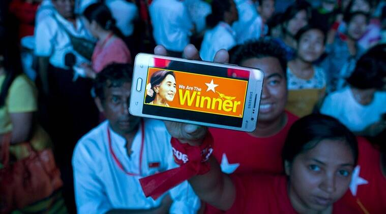 A supporter of Myanmar's National League for Democracy party displays her mobile phone with a picture of Suu Kyi as they gather to celebrate unofficial election results outside the NLD headquarters in Yangon, Myanmar, Monday, Nov. 9, 2015. Opposition leader Aung San Suu Kyi's NLD party said Monday that it was confident it was headed for a landslide victory in Myanmar's historic elections, and official results from the government that began trickling in appeared to back up the claim. (AP Photo/Gemunu Amarasinghe)