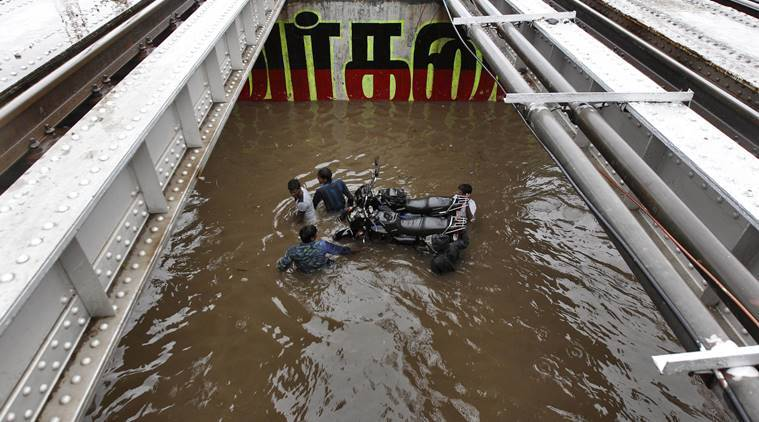 Commuters carry their motorbikes on a submerged cart as they wade through a waterlogged subway in Chennai. (Source: AP photo)
