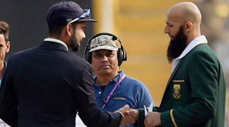 Mohali: Indian Captain Virat Kohli shakes hands with South African captain Hashim Amla  during the toss of first Test match in Mohali on Thursday. PTI Photo by Manvender Vashist(PTI11_5_2015_000005A)