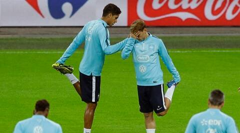French national soccer team player Antoine Griezmann, right, whose sister escaped from the concert hall where over 80 people lost their lives in the Paris attacks, stretches with Raphael Varane as they take part in a training session with their teammates at Wembley Stadium in London, Monday, Nov. 16, 2015. Three days after being caught up in a synchronized terrorist attack in Paris that resulted in the death of over 120 people, France's players have travelled to London to play a friendly soccer match against England at Wembley Stadium, where there will be a beefed-up security presence and increased checks outside the ground. (AP Photo/Matt Dunham)
