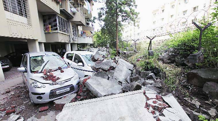 Damaged cars at Gagan Vihar Society, near Market Yard, after the society wall collapsed due to heavy downpour on Sunday night. (Pavan Khengre)