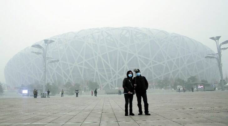 Visitors take a selfie at the National Stadium as the choking smog continues to blanket Beijing on Tuesday. All schools in the Chinese capital have been ordered to keep students indoors due to the heavy smog. Reuters
