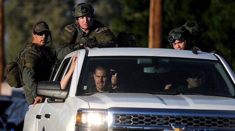 Authorities search an area Wednesday, Dec. 2, 2015, following a shooting that killed multiple people at a social services center for the disabled in San Bernardino, Calif. (James Quigg/The Victor Valley Daily Press via AP)