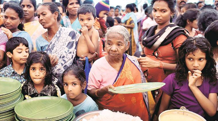 People wait for food at a relief camp in Chennai,Thursday. (Source: PTI)