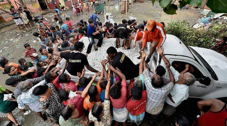 Chennai: NDRF volunteers distributing free milk packets to residents of Kotturpuram, one of the worst flood-hit localities in Chennai on Saturday. PTI Photo (PTI12_5_2015_000177B)