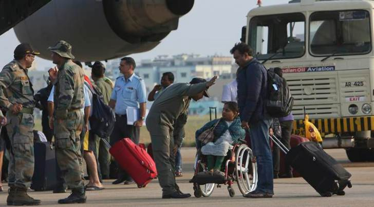 An Indian Air Fore officer talks to Indian woman Preethi Gupta, on wheel chair, as passengers who were stranded in Chennai due to the floods were rescued in an Indian Air Force C-17 aircraft and brought to the Begumpet Air Force Station, in Hyderabad, India, Thursday, Dec. 3, 2015. The heaviest rainfall in more than 100 years has devastated swathes of the southern Indian state of Tamil Nadu, with thousands forced to leave their submerged homes and schools, offices and a regional airport shut for a second day Thursday. (AP Photo/Mahesh Kumar A.)